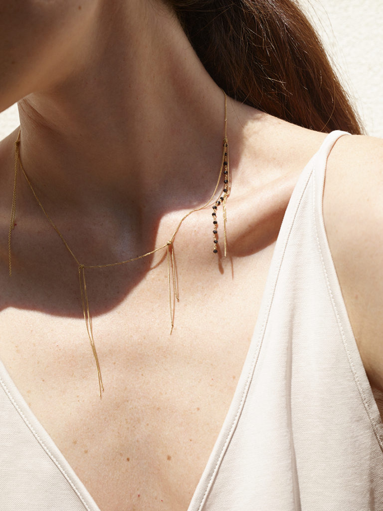 Fringe necklace in 18KT yellow gold and black spinels worn by a female neck – Frange