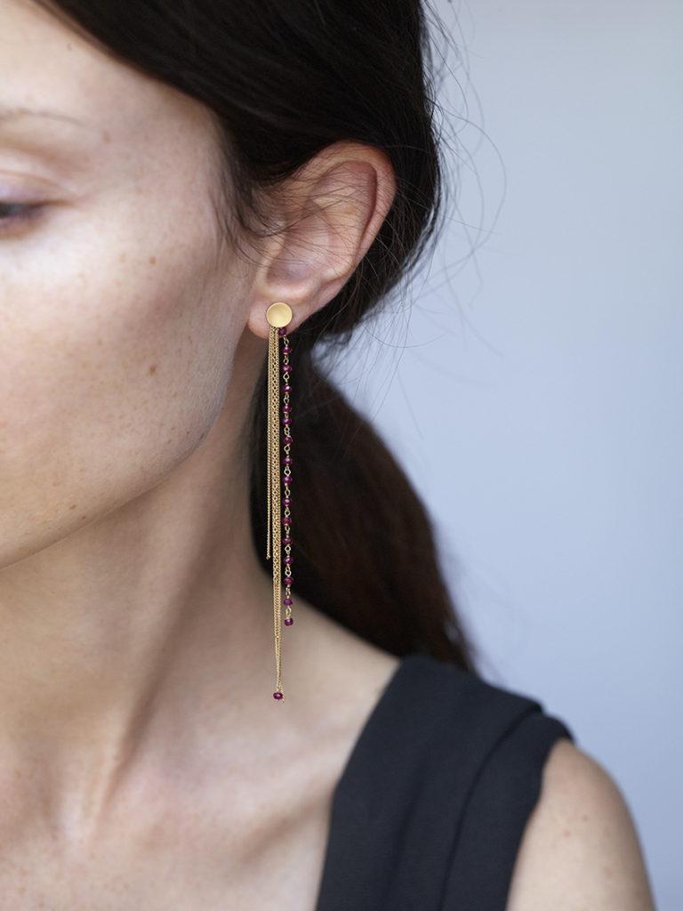 Fringe earrings in 18KT yellow gold with rubies worn by a female ear - Frange Rubino