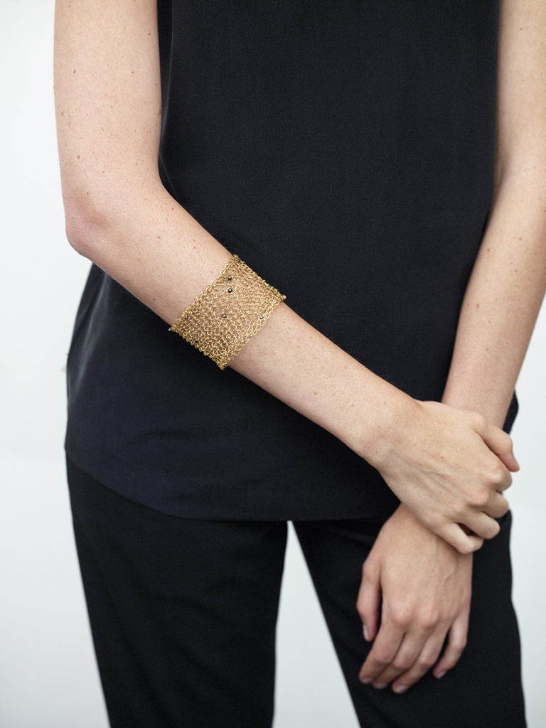 18KT yellow gold cuff bracelet with black spinels worn by female hand - Mesh